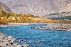 Herbstszene des blauen Wassers von Gilgit-Fluss durchfließendes Gupis, Ghizer, Pakistan stockbilder