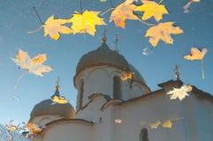 Herbstszene - Reflexion in einer Pfütze von Kathedrale St. Sophia mit gefallenem Herbstlaub in Veliky Novgorod, Russland Stockfotografie