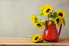 Herbsttapete Sonnenblumen im roten Vase auf Holztisch Stockbilder