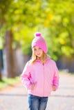 Herbstwinter-Kindermädchen blond mit Jeans und rosa Schneekappe Stockfoto