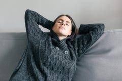 Herbstwinterporträt des jungen Mädchens zu Hause stillstehend auf Sofa in der warmen Kleidung stockfoto