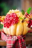 Herbstzusammensetzung eines Kürbises mit Blumen Stockbild