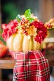 Herbstzusammensetzung eines Kürbises mit Blumen Stockfoto