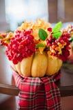 Herbstzusammensetzung eines Kürbises mit Blumen Stockfotos