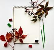 Herbstzusammensetzung mit dem Album, Aquarellen und Bürsten, verziert mit roten Blättern und Beeren Flache Lage, Draufsicht Stockfoto