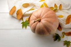 Herbstzusammensetzung mit Gelbblättern und ein warmer Schal und ein Kürbis Autumn Time Auf einem weißen Holztisch stockfoto