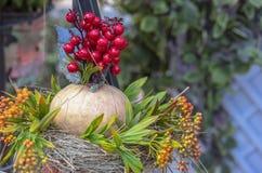 Herbstzusammensetzung mit Kürbis, Blumen und roten Beeren lizenzfreies stockfoto