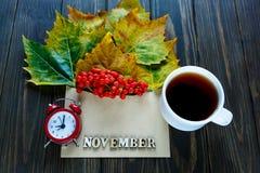 Herbstzusammensetzung mit Umschlag und Blätter, Beeren in ihm nahe bei Wort November durch Buchstaben, rote Uhr und Tasse Kaffee stockfotos