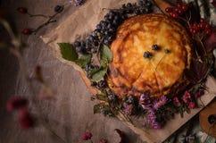 Herbstzusammensetzung von den Blumen, von den Beeren und vom gelben Kuchen Stockfoto