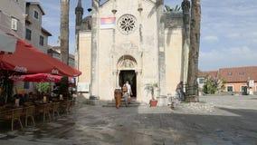 Herceg Novi, Montenegro - 31 de junho de 2017 St Michael Archangel Herceg Novi da igreja Os turistas do homem e da mulher são bat vídeos de arquivo