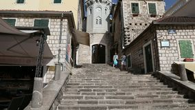 Herceg Novi, Montenegro - 31 June, 2017. Pair of girls tourists climb by stairs to Topla tower with clock of old city stock video