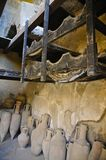 Herculaneum, Campania, Italy. Charred wood and Amphorae in a Herculanean Tavern Interior, in portrait mode Stock Images