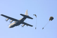 Hercules plane drops parachute troopers Royalty Free Stock Images