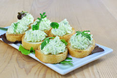 Herded cream cheese with arugula canapes on white plate Royalty Free Stock Photos