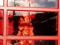 Herdenkingsrozen in een telefooncel Stock Fotografie