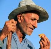 Herdsman. A kurdish herdsman eating a peach with his hand while smiling. kurdistan, iraq stock photography