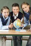 Here we are. Two, young girls and one boy standing over globe and showing something. Looking at camera, front view Royalty Free Stock Photos