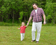 Here we come. Father and Son walking towards the camera. Son is holding a dandelion royalty free stock images