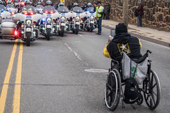 Here comes the Parade!. Washington, DC - January 16, 2017: A man in a wheelchair snaps a photo of the motorcycle police escorting the Martin Luther King, Jr. Day stock photography