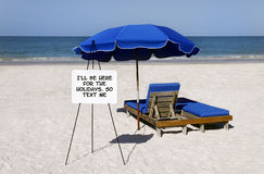 Here for the Holidays. Blue umbrellas and beach chairs with a whiteboard that says, I'll be here for the holidays, so text me Royalty Free Stock Image
