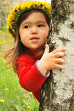 Here I am. Little girl wearing a dandelion diadem near a tree Royalty Free Stock Photography
