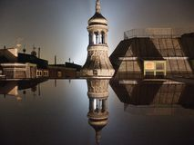 Belfry at night with moon, light, shadow and reflection royalty free stock images