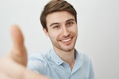 Here, let me lend you hand. Portrait of charming friendly caucasian man pulling hand towards camera as if trying to grab stock photo