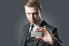Here, look!. Young businessman with holding up his blank white card card to show his credentials and qualification. Isolated on gray stock photography