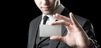 Here, look!. Young businessman with holding up his blank white card to show his credentials and qualification. Isolated on black royalty free stock image
