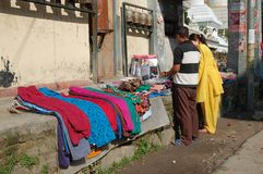 Two outdoor shoppers in Kathmandu, Nepal. Here are a man and woman shopping for clothing at an outdoor stall in Kathmandu, Nepal Royalty Free Stock Photography