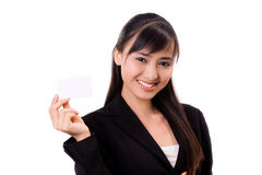 Here is my card. Young pretty successful asian female executive with a white card Royalty Free Stock Photos