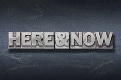 Here and now den. Here and now phrase made from metallic letterpress on dark jeans background royalty free stock image
