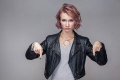 Here and right now. Portrait of bossy serious beautiful girl with short hair, makeup, casual style black leather jacket standing. And looking at camera. indoor stock image