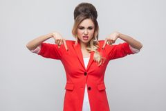 Here and right now. Serious beautiful business lady with hairstyle and makeup in red fancy blazer, standing, looking at camera and. Pointing down side. studio stock photo