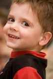 Here's Looking at You. A bright-eyed preschooler looking over his shoulder at the viewer Stock Photography