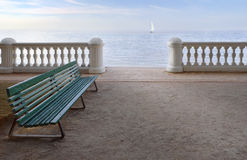 Here& there. Lonely bench on a background of sea and a lonely sail Stock Images