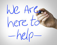 We are here to help hand writing on blue marker on transparent wipe board.  Stock Photo