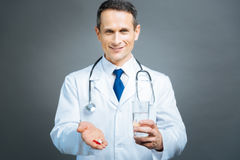Mindful male doctor brining pills and water Royalty Free Stock Photography