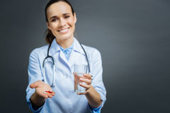 Mindful female doctor brining pills and water Royalty Free Stock Photos