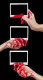 Here are your photos. A composite of 3 blood covered hands holding up pieces of blank instant film isolated on black Stock Photo