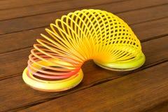 Herein gefilmt am 1. September 2018 in Gomel Spielzeugplastikregenbogen auf einem Holztisch Mehrfarbige Spirale f?r das Spiel lizenzfreies stockfoto