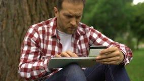 Hereinkommende Kreditkartennummer des Mannes auf Tablette, parkende on-line-Rechnungen und Geldstrafen zahlend stock video