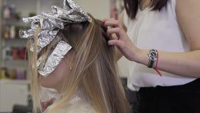 Herenkapper die haar kleurende kleurstof toepassen om haartoon omhoog te verlichten stock video