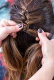 Herenkapper die het bruine haar van een vrouw vlechten Stock Afbeeldingen