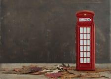 Herfstbeeld met droge esdoornbladeren en rode Britse telefooncel Royalty-vrije Stock Afbeeldingen