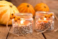 Herfstdecoratie - thee lichte glazen en pompoenen Stock Foto's