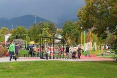 Herfstzondag in de speelplaats: ouders en kinderen die pret hebben samen in openlucht Heidelberg, Duitsland - Oktober 8 2017 Royalty-vrije Stock Afbeeldingen