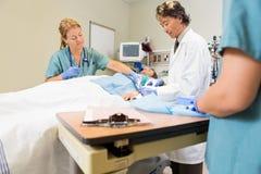 Herida del doctor Stitching Male Patient mientras que enfermera Fotografía de archivo