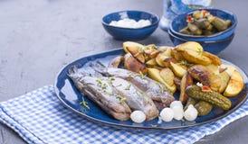 Heringsfilets auf einer Platte, gebacken in den Ofenkartoffeln und die in Essig eingelegten Gurken und die Zwiebeln Köstliches tr stockbild