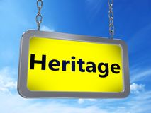 Heritage on billboard. Heritage on yellow light box billboard on blue sky background Royalty Free Stock Image